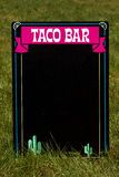 Taco Bar. A taco bar chalkboard sitting in the grass Royalty Free Stock Photography