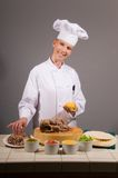 Taco Chef. Portrait of a kitchen working attractive uniformed female Chef in the process of making a pork taco Royalty Free Stock Photo