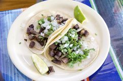 Taco de Lengua. Traditional mexican beef tongue lengua tacos with lime wedges Stock Photo