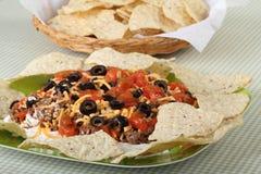 Taco Dip. Consisting of hamburger, cheese, black olives, and tomatoes with tortilla chips Stock Photos