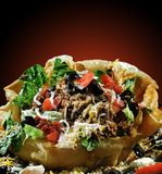 Taco Salad in Shell. Colorful taco salad in fried tortilla shell on black background with red spotlight effect. Beef, black olives, cheese, lettuce, tomatoes Royalty Free Stock Photos