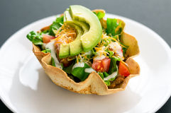 Taco tortilla salad. A taco salad in tortilla bowl is a fun and colorful way to eat mexican food. Made with fresh ingredients such as avocado, tomatoes, green Stock Photography