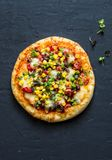 Taco vegetarian pizza. Mexican pizza with beans, corn, jalapeno pepper, mozzarella cheese on a dark background, top view. Snack, tapas Royalty Free Stock Photos