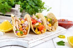 Taco - wheat tortilla with meat, vegetables, corn, greens. Delicious mexican snack. On a white wooden background. Street food stock images