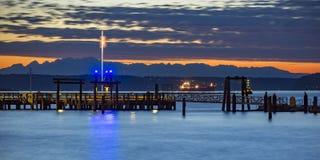 Tacoma pir med fartyg- och bergsikt på solnedgången arkivfoto