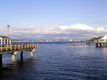 Tacoma Waterfront. A fishing pier and a restaurant pier in the foreground; industrial docks in the distance. Located on the waterfront in Tacoma, Washington. The Royalty Free Stock Photos