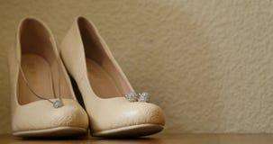 Tacones altos beige elegantes lindos en el cuarto del fondo, encanto, moda, casandose metrajes
