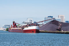 Taconite Unload. A Great Lakes self discharging bulk carrier vessel unloads taconite pellets at the Cleveland Bulk Terminal inside the harbor at Cleveland, Ohio stock images