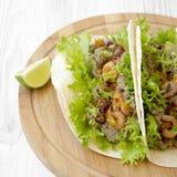 Tacos del camarón en tablero de bambú redondo en el fondo de madera blanco, vista lateral Comida mexicana primer imagenes de archivo