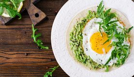 Tacos with guacamole, fried egg and arugula. Healthy food. Useful breakfast. Flat lay. Top view stock photos