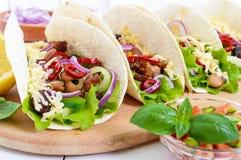 Tacos ist ein traditioneller mexikanischer Teller Tortilla angefüllt mit Huhn, Glocke und Peperoni, Bohnen, Kopfsalat, Käse stockfotos
