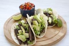 Tacos mexicanos com salsa na placa de bambu em um fundo de madeira branco, vista lateral foto de stock royalty free