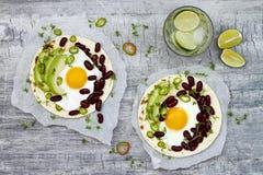 Tacos mexicanos de los rancheros de los huevos Tostadas del desayuno con las alubias negras, aguacate, huevo frito, microgreens,  Foto de archivo