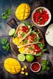 Tacos mexicanos del camarón con el aguacate, tomate, salsa del mango en la tabla de piedra rústica Receta para el partido de Cinc imagenes de archivo