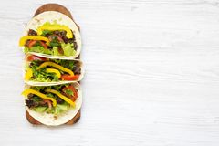 Tacos with pork and vegetables. Mexican kitchen. White wooden background. stock photography