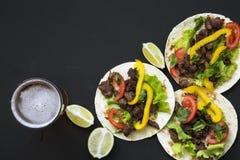 Tacos saborosos com carne e vegetais, cerveja e cal em um fundo preto, vista superior Cozinha mexicana Imagens de Stock