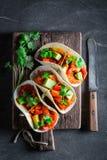 Tacos savoureux avec de la sauce épicée et la coriandre fraîche Photographie stock libre de droits