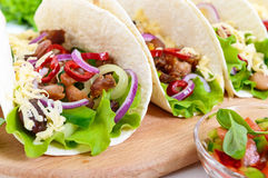 Tacos is a traditional Mexican dish. Tortilla stuffed with chicken, bell and hot peppers, beans, lettuce, cheese, blue onion Stock Photo