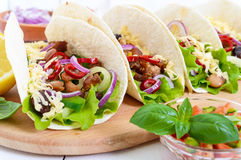 Tacos is a traditional Mexican dish. Tortilla stuffed with chicken, bell and hot peppers, beans, lettuce, cheese Stock Photos