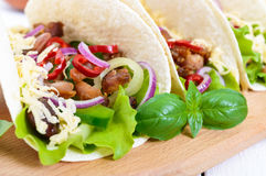 Tacos is a traditional Mexican dish. Tortilla stuffed with chicken, bell and hot peppers, beans, lettuce, cheese Stock Photography