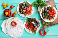 Tacos vegetarianos con la berenjena, tomates de cereza, pimientas dulces en un fondo de madera brillante Imágenes de archivo libres de regalías
