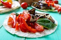Tacos vegetarianos con la berenjena, tomates de cereza, pimientas dulces en un fondo de madera brillante Imagen de archivo libre de regalías