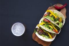 Tacos z piwem na desce na czarnym drewnianym tle, odgórny v obraz royalty free