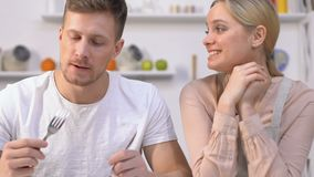 Tactful guy trying girlfriends tasteless dish, pretending that it is delicious. Stock footage stock video