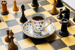 Tactic and strategy of modern life in concept. Cup of coffee on chessboard Stock Image