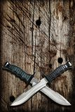Tactical Combat Hunting Survival Bowie Knives With Crossed Blades On Grunge Vignetted Old Battered Grooved Wood Background.  Stock Images