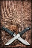Tactical Combat Hunting Survival Bowie Knives With Crossed Blades On Grunge Vignetted Old Battered Grooved Wood Background.  Stock Photography