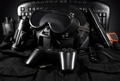 Tactical gear & gamepad. Tactical helmet, gloves, gun, binoculars laying on a jacket with gamepad & keyboard on background Royalty Free Stock Photo