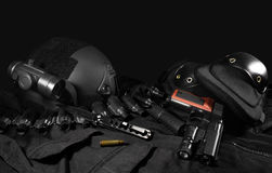 Tactical gear laying composition. Black military ammunition tactical gun, helmet, gloves, cartridge belt, bandolier, gun shell, knife, binocular and knee Royalty Free Stock Photo