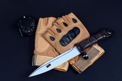 tactical gloves  bayonet and compass on black background