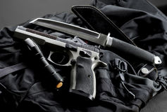 Tactical gun. With knife and flashlight on black backpack stock image