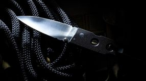 Tactical knife. Folding self defense knife that is on a black rope stock image