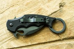 Tactical knife with clip in a folded position on a wood background. Royalty Free Stock Photography
