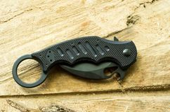 Tactical knife in a folded position on a wood background. Royalty Free Stock Photography