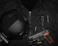 Tactical military gear upper view. Photo of a tactical helmet, gun shells, hand gun, knife & flashlight  laying on a black swat vest Stock Images