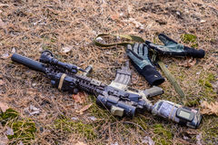 Tactical semi automatic rifle and gloves on ground in the forest. Automatic rifle with tactical flashlight, telescopic sight and soldiers gloves lie on the royalty free stock photography