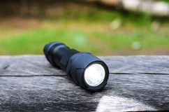 Tactical waterproof flashlight on wooden base with light beam Royalty Free Stock Photos