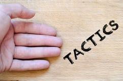 Tactics text concept. Human hand over wooden background and tactics text concept Stock Photography