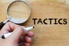Tactics text concept. Human hand over wooden background and tactics text concept Stock Photo