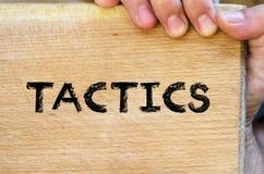 Tactics text concept. Human hand over wooden background and tactics text concept Stock Image