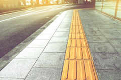 Tactile paving for blind handicap on tiles pathway. Royalty Free Stock Image