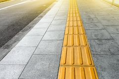 Tactile paving for blind handicap on tiles pathway. Walkway for blindness people Stock Photo