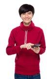 Tacto asiático del hombre joven en el teléfono móvil Imagen de archivo