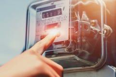 Tacto de la mano en el metro del vatio-hora foto de archivo