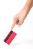 Tacto de la mano en tarjeta de crédito roja Foto de archivo libre de regalías