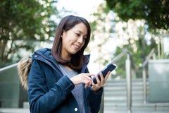 Tacto de la mujer en el teléfono móvil imagenes de archivo